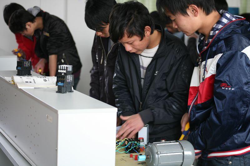理工教师张泉对机电班学生上电工实训课。通过实训培养学生的操作技能,使学生全面掌握电工的基本知识、基本操作、电路的合理布局和安装工艺,同时使学生通过电工基本操作技能训练,注意与生产劳动相结合,重视专业培养,打造良好的专业基础。