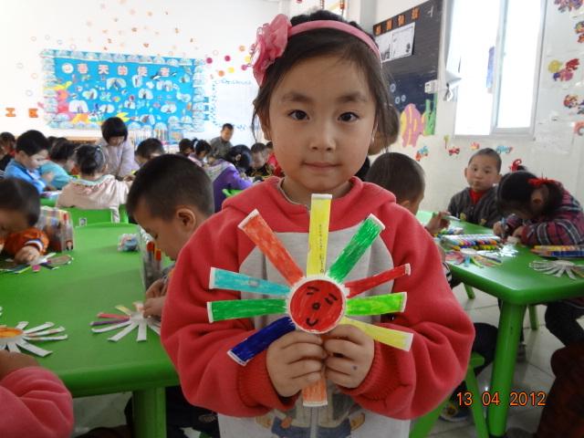 我们剪出了漂亮的花瓣,涂上了鲜艳的颜色,还画上了可爱的笑脸呢,作出